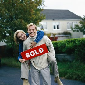 portrait of a couple holding a sold sign